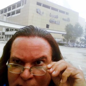 Maverick Artist Victor-Hugo Vaca II In Front Of Skeletal Remains Of The Miami Herald Building Before It Is Imploded, Bulldozed & Scrapped Due To Declining Public Trust In Reporting & Declining Sales & Circulation